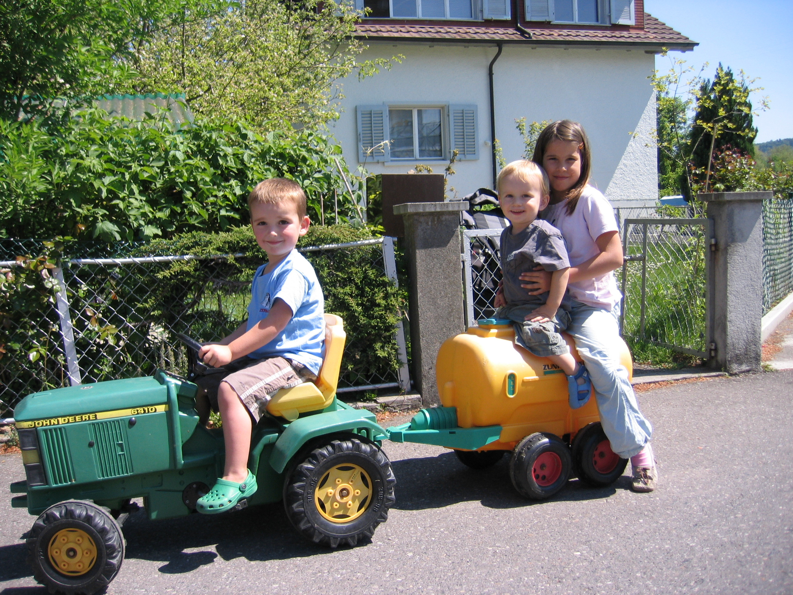 Toby, Noah and Julia on a tractor outside our house in Oberentfelden